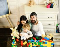 Mom, dad and boy play with white soft toys. On room background. Parents and son with cheerful faces near colorful blocks for building. Young family spends time royalty free stock photo