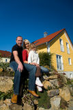 Mom, Dad, child. A young couple with their daughter sitting in front of their yellow home stock image