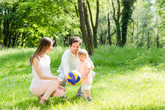 Mom, dad, and child playing with ball Royalty Free Stock Photos