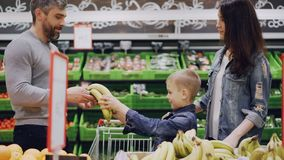 Mom, dad and cute boy are choosing fruit in food store, child is smelling bananas and giving them to his father, man is. Putting fruit in shopping trolley. Food stock footage