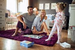 Mom and dad with cute kid. In living room stock images