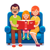 Mom, dad and daughter reading story book together. Family. Mom, dad and daughter reading story book together sitting on the couch. Happy parents with their kid Royalty Free Stock Photo