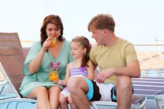 Mom, dad and daughter rest on deck and drink juice Stock Photography