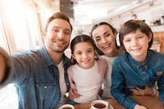 Mom, dad, daughter and son posing together on a camera in a cafe. A young family came together in a cafe. Mom, dad, little daughter and son drink tea, eat cakes royalty free stock photos