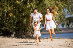 Mom, dad and daughter walking on the beach Royalty Free Stock Image
