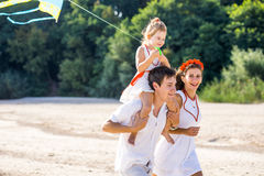 Mom, dad and daughter walking on the beach Stock Photography