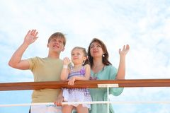Mom, dad and daughter wave by hands to ship Royalty Free Stock Images