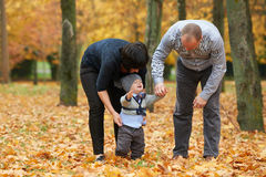 Mom and dad disguised child in park Stock Images
