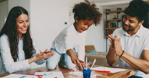 Mom and dad drawing with their daughter. Mom and dad drawing with their daughter at home royalty free stock image