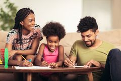 Mom and dad drawing with their daughter. African american family spending time together at home stock image