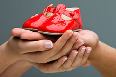 Mom and Dad Expecting a baby. Woman and her husband holding baby shoes in their hands. Mom and Dad Expecting a baby royalty free stock photo