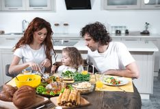 Mom and dad feeding little daughter in kitchen royalty free stock photography