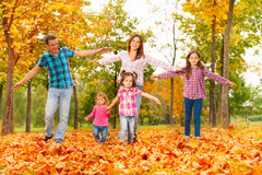 Mom dad and girls play in autumn park. Happy family mom, dad and three little girls play run and show airplane with hands in autumn park royalty free stock photos