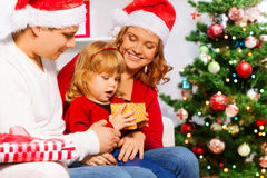 Mom and dad give New year presents to happy girl. Family with mom dad and little three years old daughter sitting near Christmas tree and opening New year stock images