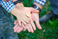 Mom and Dad hold baby's hand Stock Image