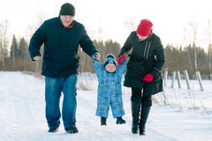 Mom and Dad hold baby`s hands walk in winter park Royalty Free Stock Photos
