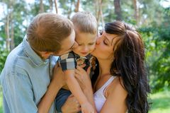 Mom and Dad hug and kiss their baby Royalty Free Stock Photos