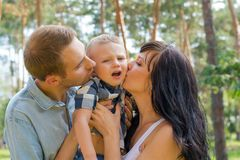 Mom and Dad hug and kiss their baby, and he`s naughty. Royalty Free Stock Image