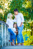 Mom, Dad and kid laughing hugging, enjoying nature Stock Photo