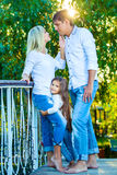 Mom, Dad and kid laughing hugging, enjoying nature. Mom, Dad and kid laughing and hugging, enjoying nature outside. in blue jeans and white shirts Royalty Free Stock Images