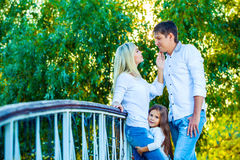 Mom, Dad and kid laughing hugging, enjoying nature Stock Photos