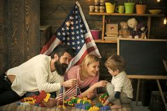 Mom, dad and kid play with colorful plastic blocks. Smiling parents leaning towards son on sofa. Family over American. Flag background. Dad passing toy flags to royalty free stock images