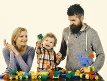 Mom, dad and kid in playroom. Man with beard, woman and boy play on white background. Mom, dad and kid in playroom. Man with beard, women and boy play on white royalty free stock photography