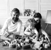 Mom, dad and kid with toys on wooden background build out of blocks. Love and family games concept. Young family spends. Time in playroom. Parents and son with royalty free stock images