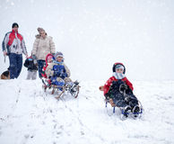 Mom, dad with kids having fun in the snow Stock Photos
