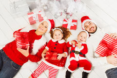 Mom dad and kids with present under Christmas tree Stock Photos