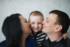 Mom and dad kiss son Royalty Free Stock Images