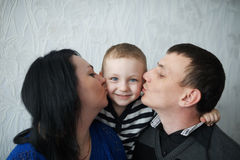 Mom and dad kiss son Royalty Free Stock Image