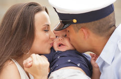 Mom and dad kissing the baby Royalty Free Stock Photography