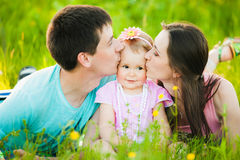 Mom and dad kissing cheeks of little daughter Stock Photo