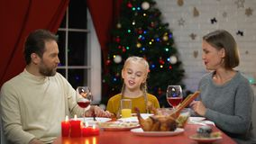 Mom and dad kissing daughter at Christmas lunch, looking to camera, holiday eve. Stock footage stock video footage