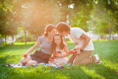 Mom and Dad kissing daughter Stock Image