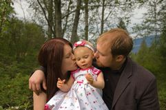 Mom and Dad Are Kissing Toddler Girl. This attractive young mom and dad are both kissing their toddler girl for a sweet family moment Royalty Free Stock Image