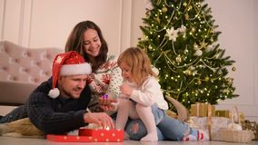 Mom, Dad And Little Baby Daughter . Loving Family Merry Christmas and Happy New Year. Cheerful Pretty People. Parents. And Child Having Fun Near Christmas Tree stock video