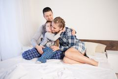 Mom and dad and little boy in the bedroom. Mom dad and son woke up in the morning Stock Images