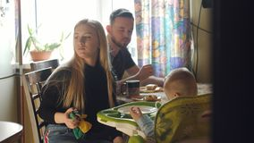 Family drinking tea in the kitchen and eat pancakes. Mom, dad and a little boy on a children`s chair drinking tea with. Mom, dad and a little boy on a children`s stock video