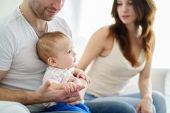 Mom, dad and little son resting in living room. Happy young family enjoy time together. Mom, dad and little baby son resting in living room. Childhood stock image