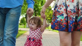 Mom and dad play with baby raise baby by hands up, little girl jumping and laughing, family walk in the Park in summer. Mom and dad play with baby raise baby by royalty free stock images