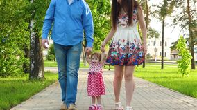 Mom and dad play with baby raise baby by hands up, little girl jumping and laughing, family walk in the Park in summer. Mom and dad play with baby raise baby by royalty free stock photography
