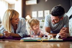 Mom and dad play with their kid in room. Cheerful mom and dad play with their kid in room royalty free stock photo