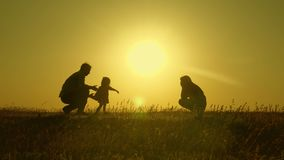 Mom and dad play with their little daughter. happy child goes from father to mother. mother and Dad play with their. Daughter in sun. young family with child of stock photo