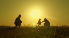 Mom and dad play with their little daughter. happy child goes from father to mother. mother and Dad play with their. Daughter in sun. young family with child of royalty free stock photo
