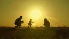 Mom and dad play with their little daughter. happy child goes from father to mother. mother and Dad play with their. Daughter in sun. young family with child of stock photography