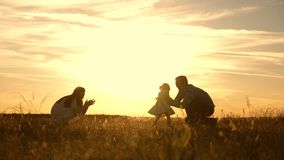 Mom and dad playing with child in park at sunset, kid takes the first steps. happy family playing with their daughter in stock video