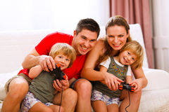Mom and dad playing with daughter on console Royalty Free Stock Photos