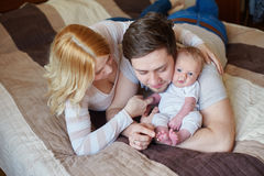 Mom and dad playing with his baby son on the bed. Happy family concept.  Royalty Free Stock Photography